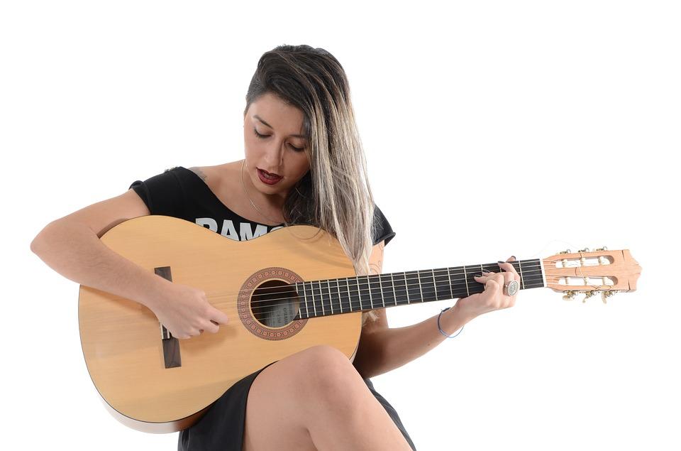 Kvinna spelar på en gitarr